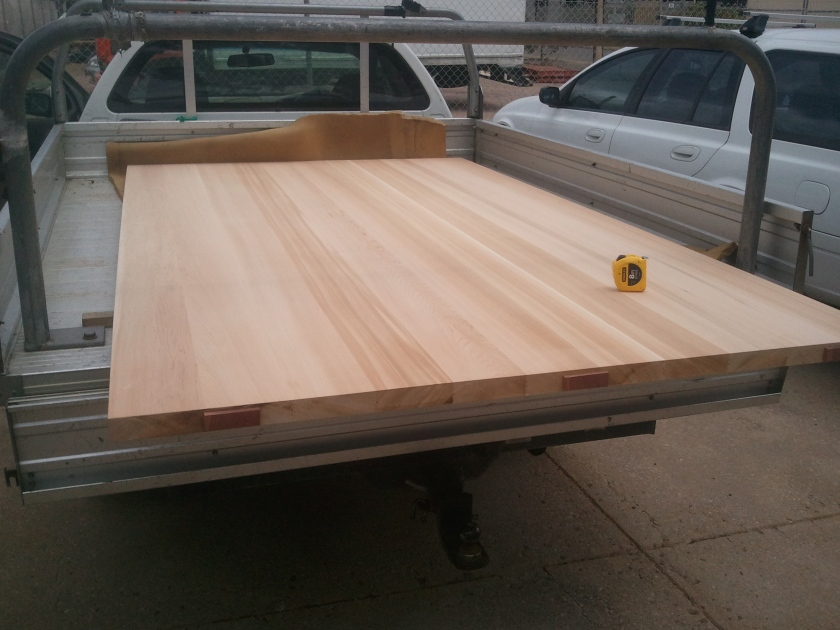 A very large timber door, barely fitting on the ute