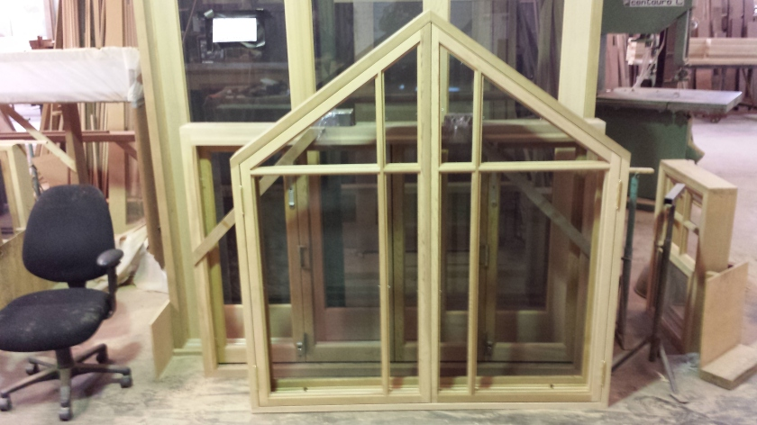 Peaked casement window with colonial bars.