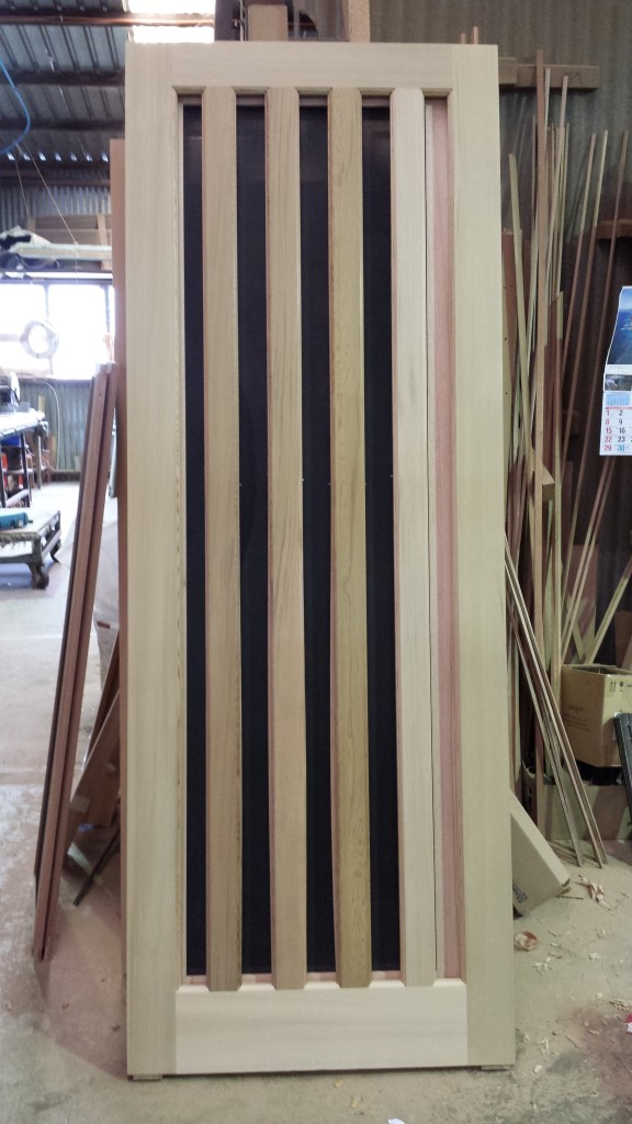 Front door with vertical slats for glass. Western red cedar.