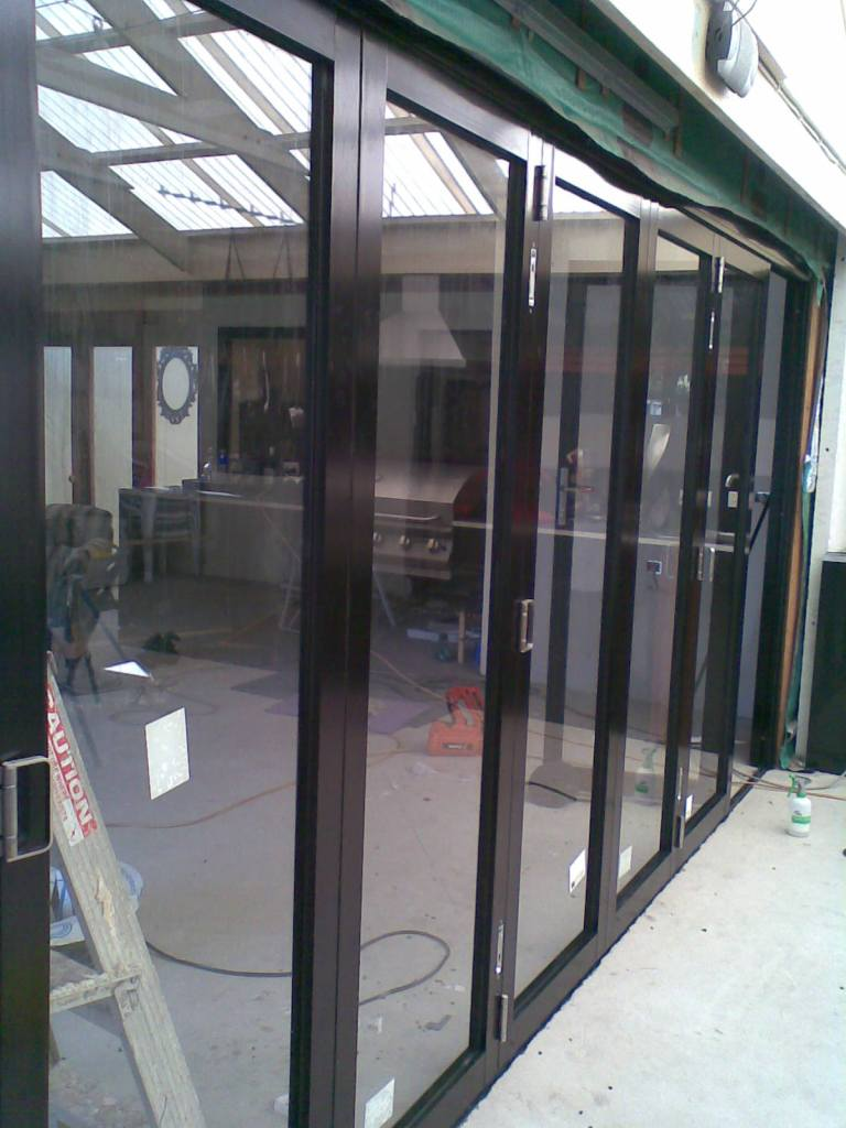 Satin black 8-panel aluminium bifold door. Internal partition.