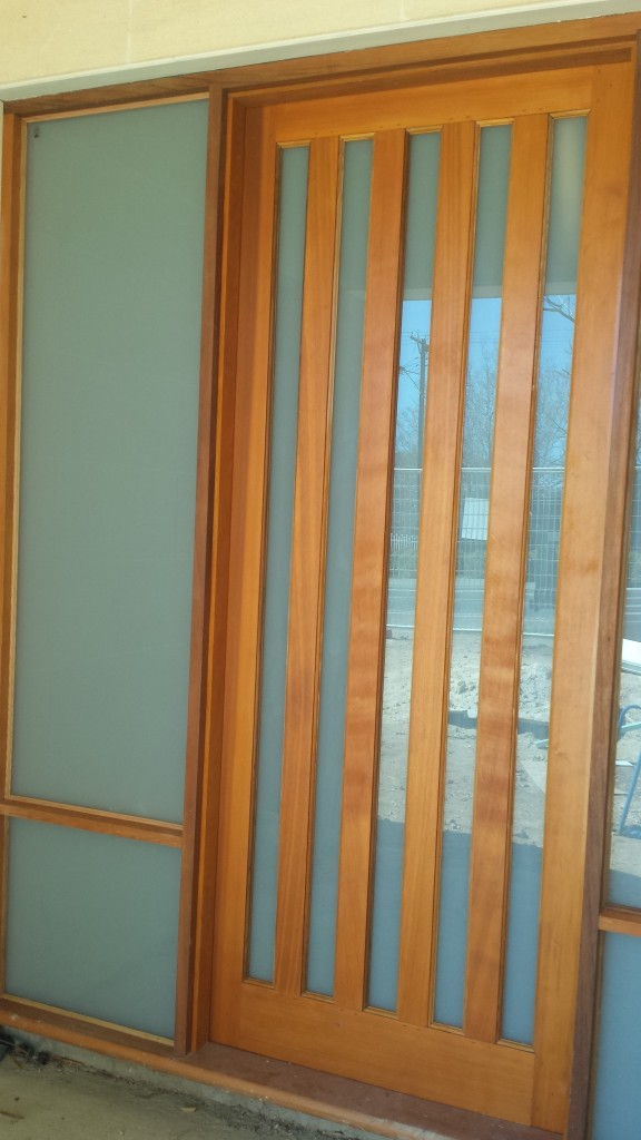 Western red cedar front door. white trans lam glass. door frame with sidelites + hardwood sill.