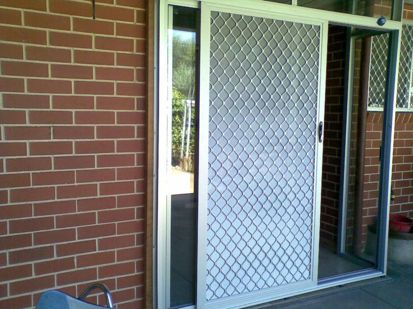 Clear anodise / natural anodise sliding door with 007 security door with DVA restricted vision mesh.