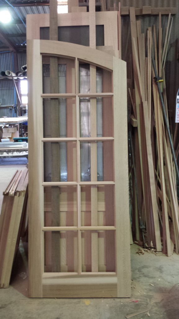 Arched WRC door with colonial bars. 1 of 2. unglazed.
