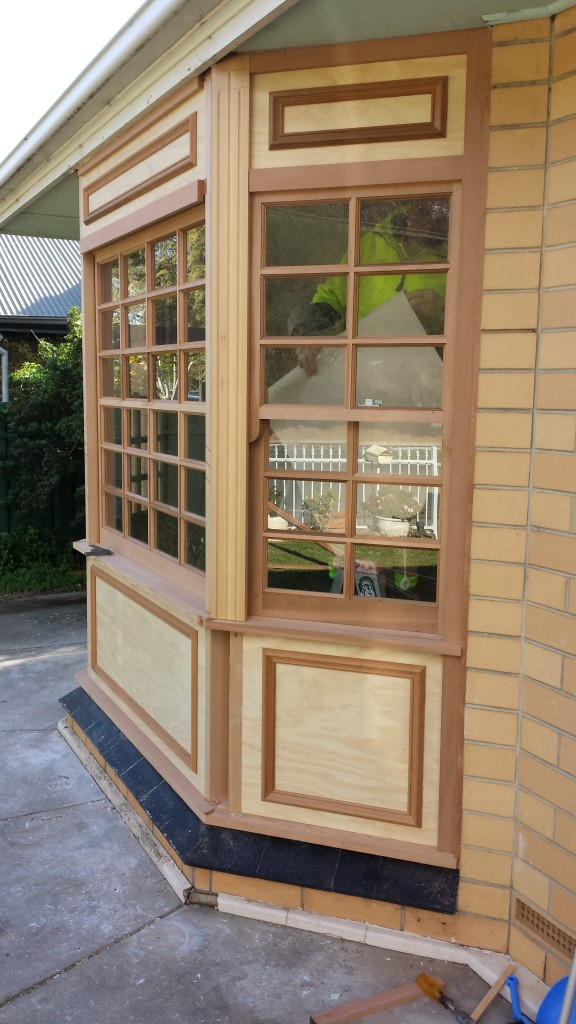 WRC bay window with colonial bars, and timber paneling.