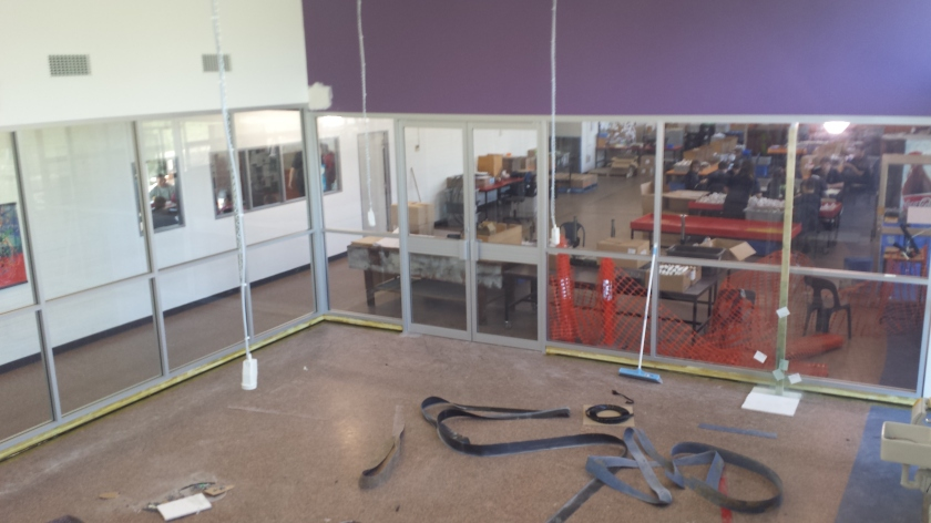 Office partition with pivot doors and clear laminate glass.