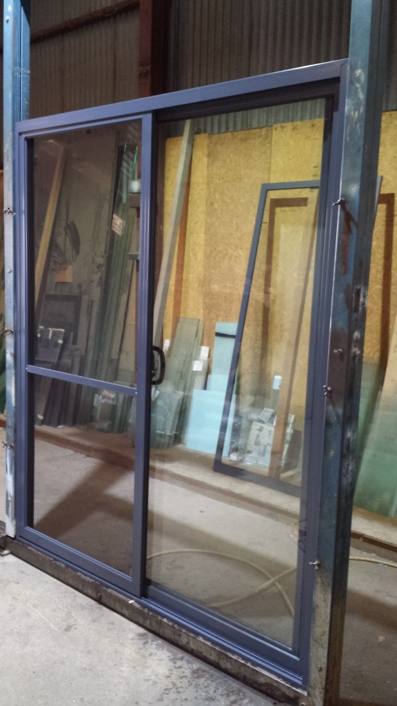 IRONSTONE powdercoat aluminium sliding door, with flydoor and clear 6.38 laminate safety glass.