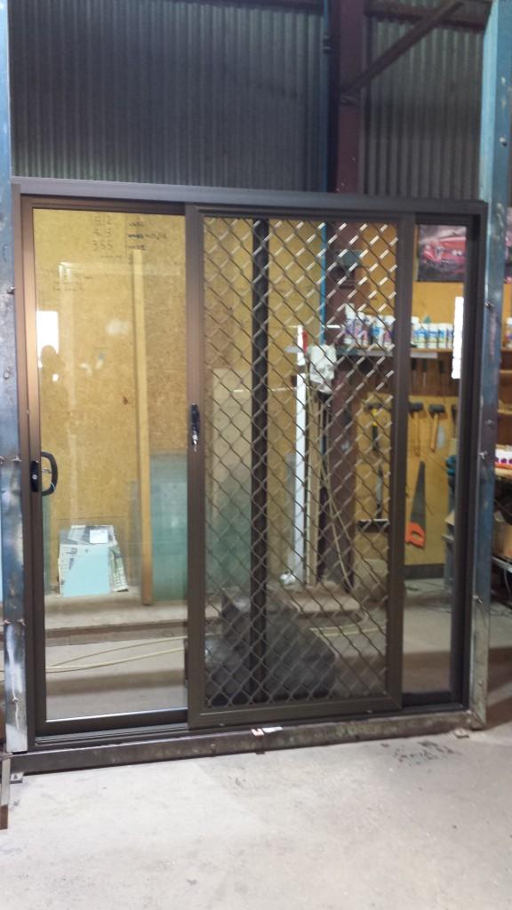 Bronze anodise sliding door with 007 diamond grille security door. 2095 high x 1810 wide