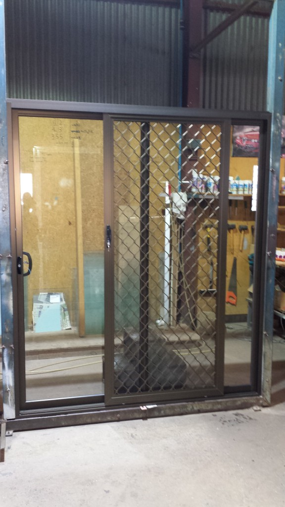 Bronze anodise sliding door with 007 diamond grille security door. 2095 high x 1810 wide