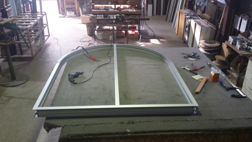 arched clear anodise aluminium fixed lite window - being assembled