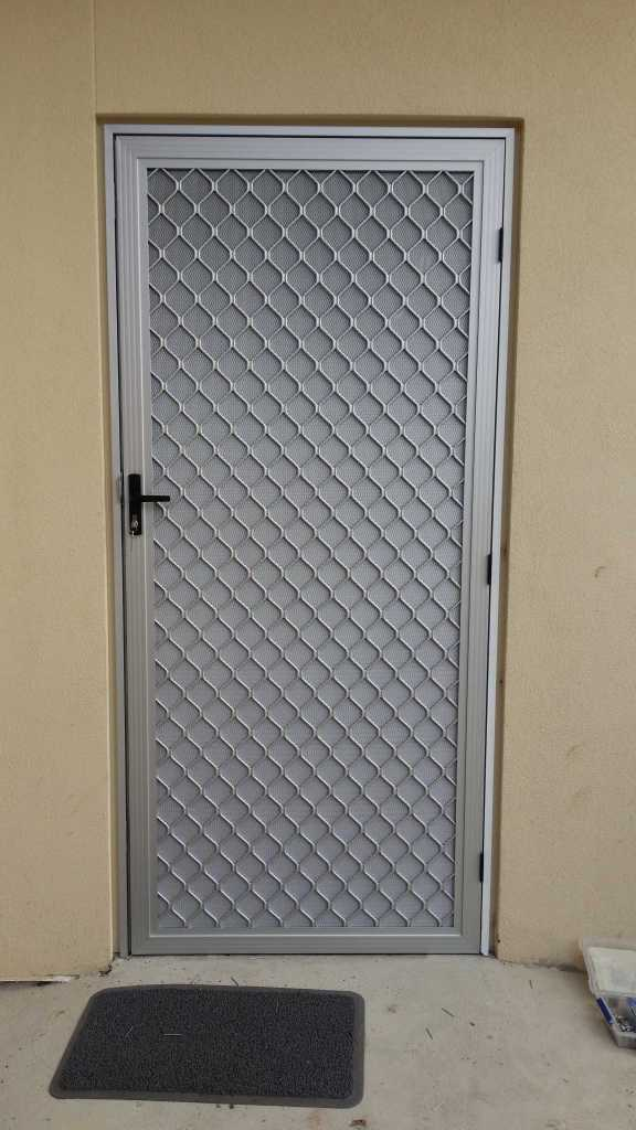 Clear anodise security door with 007 diamond grille and DVA restricted vision mesh.