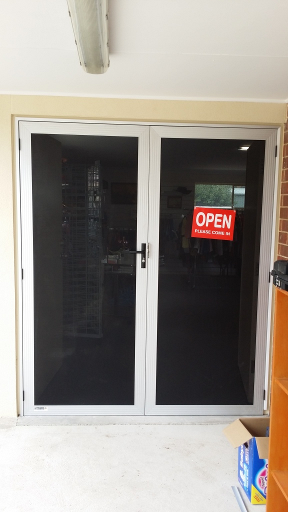 a pair of clear anodise CLEARSHIELD stainless steel security doors with frame extender on steel doorframe.