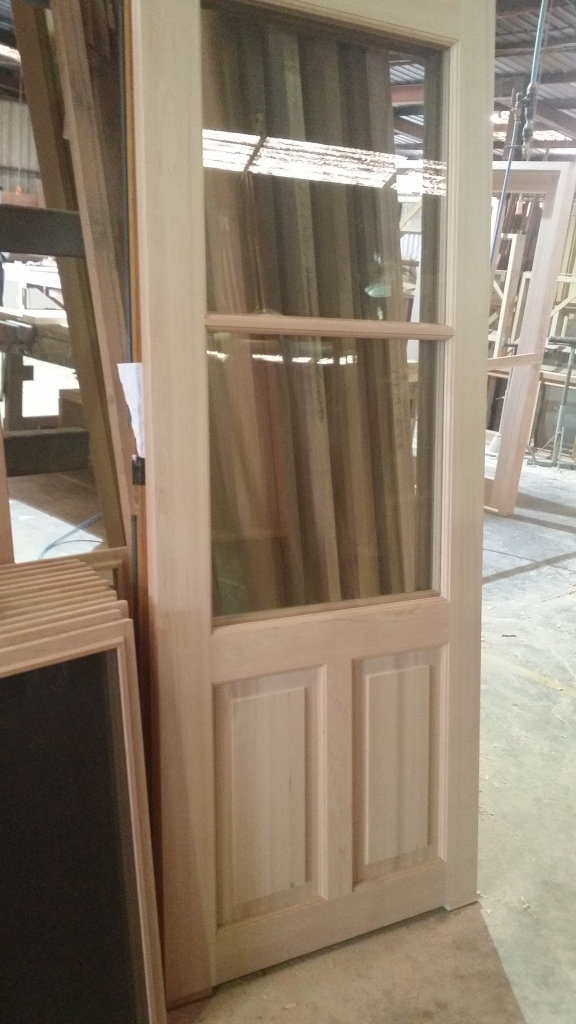 Cedar door, with clear laminate glass and recessed timber panels. 1 of a pair.