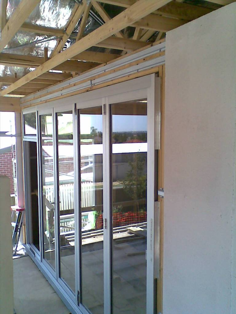Clear anodise bifold door with awning window on top of active door.